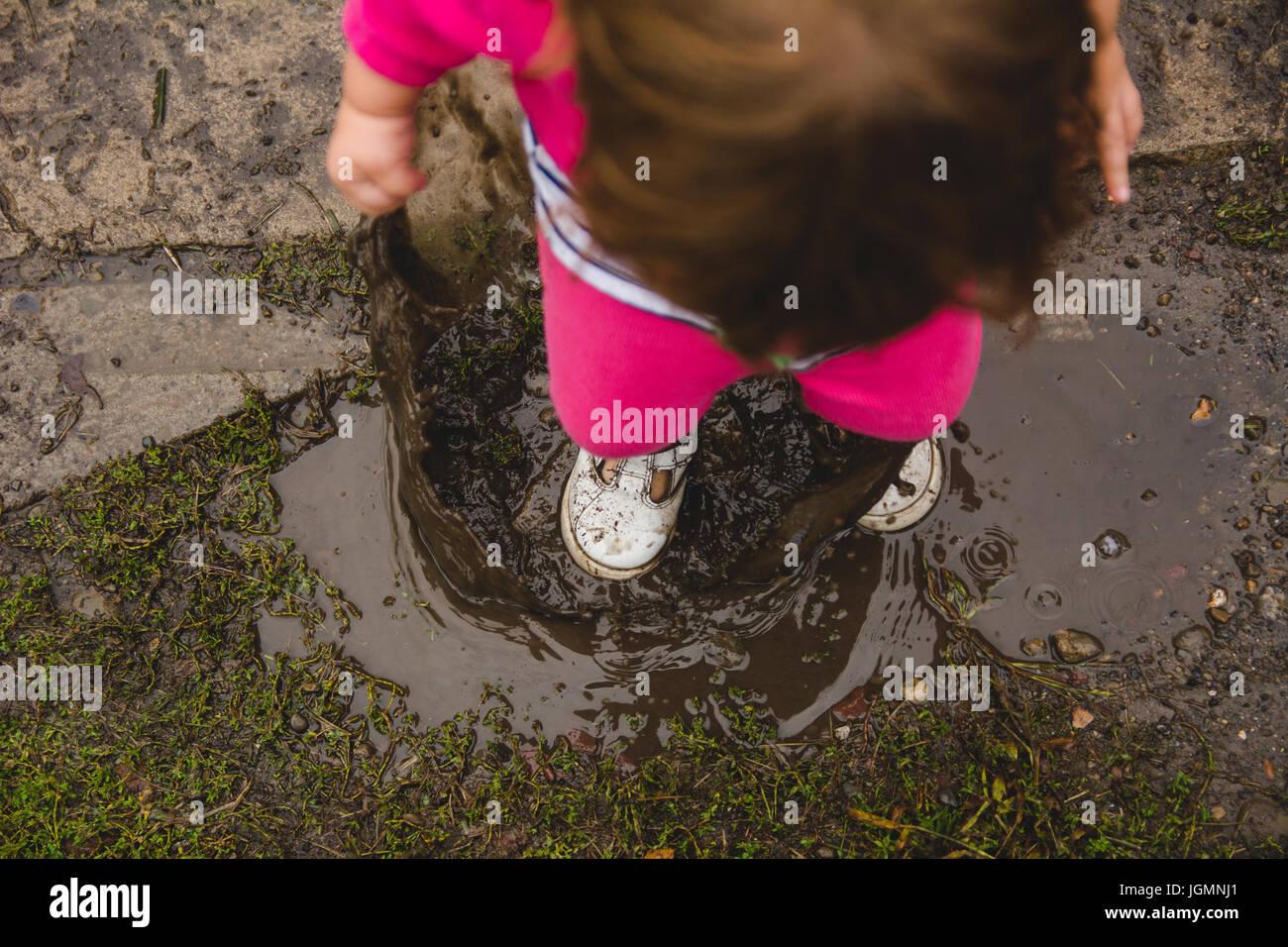 2 anno vecchia ragazza, guardando in giù a terra e Pozza di fango, spruzzi in una pozza di fango, facendo un Immagini Stock