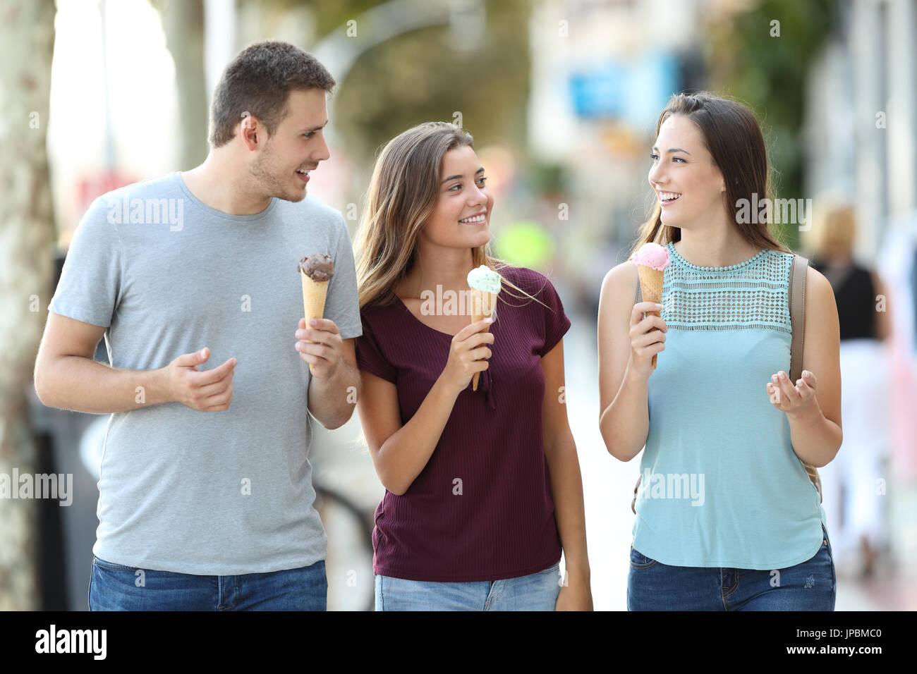 Vista frontale di tre amici felice di parlare e mangiare gelati a piedi in strada Foto Stock