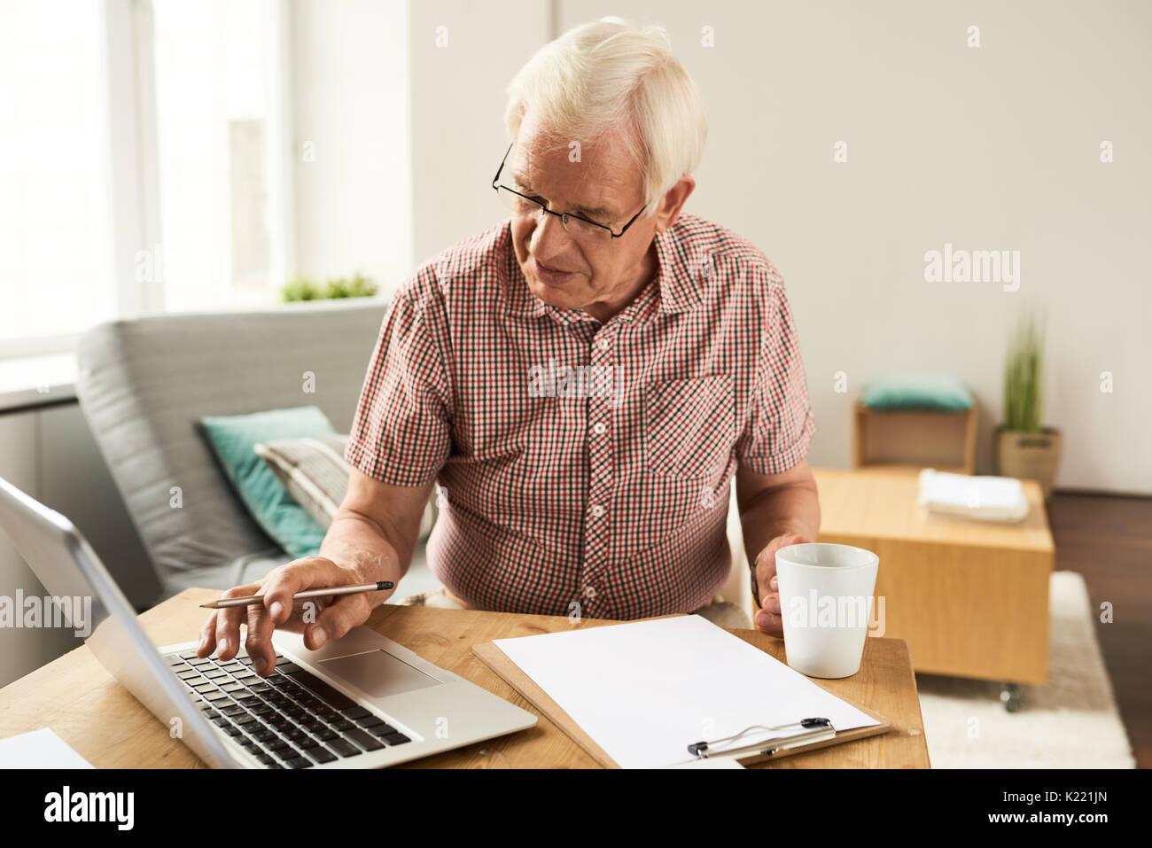 Senior uomo che lavora con il portatile a casa Foto Stock