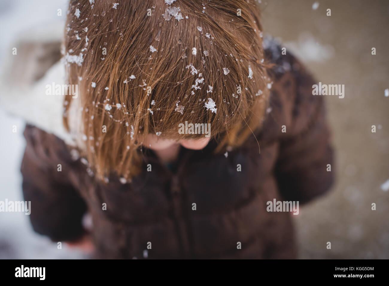 Guardando verso il basso su un bimbo che indossa un cappotto invernale con neve in i suoi capelli durante l inverno Immagini Stock