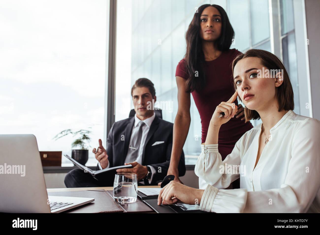 Tre imprenditori seduti alla scrivania e prestando attenzione a qualcosa di importante. giovane donna con i colleghi Immagini Stock