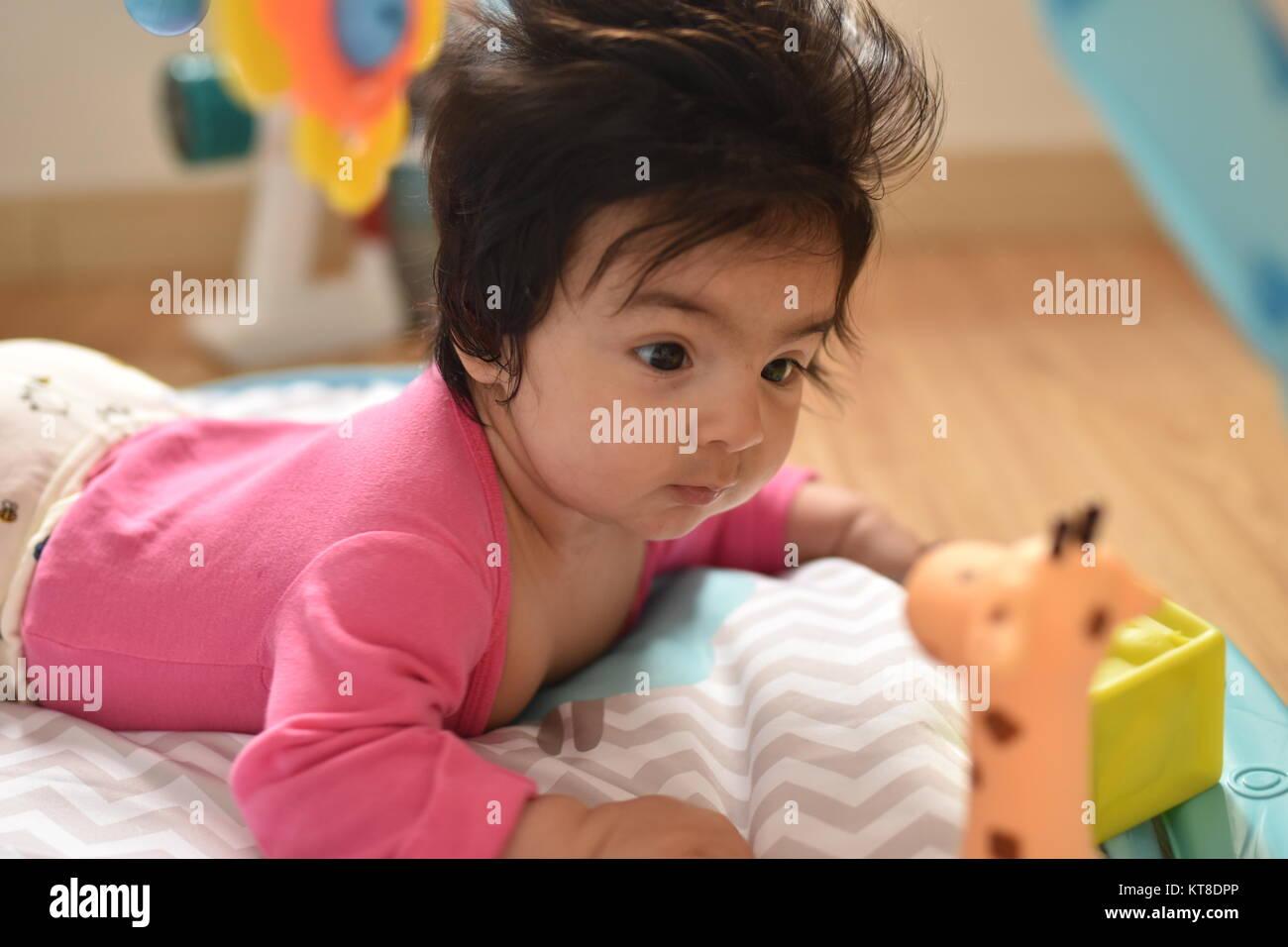 Gattona bambina guarda attentamente esaminando i suoi giocattoli Immagini Stock