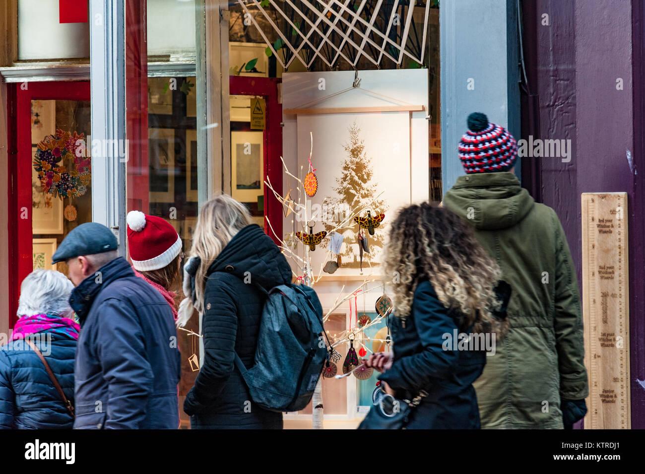 I turisti prestando attenzione a decorato per il Natale vetrina di un negozio Immagini Stock