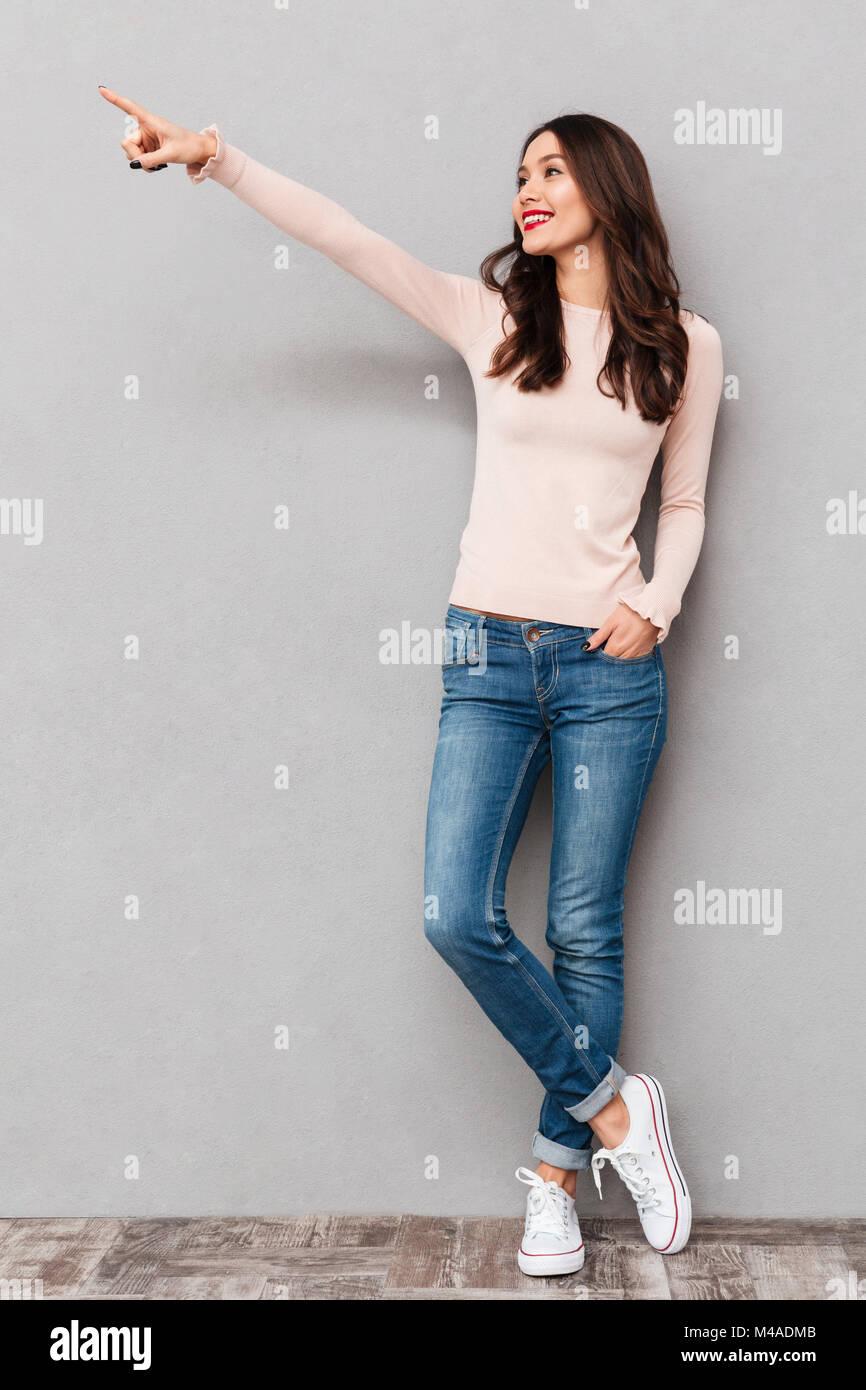 A tutta lunghezza immagine positiva di adulto ragazza con capelli castani puntare il dito indice a parte che mostra Immagini Stock