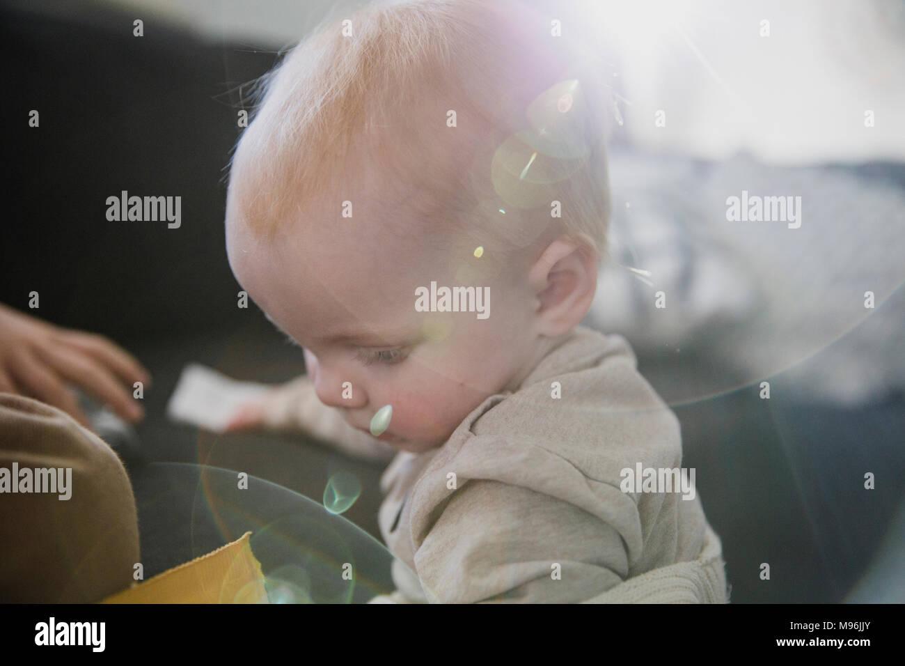 Baby guardando in giù con sun lampante Immagini Stock