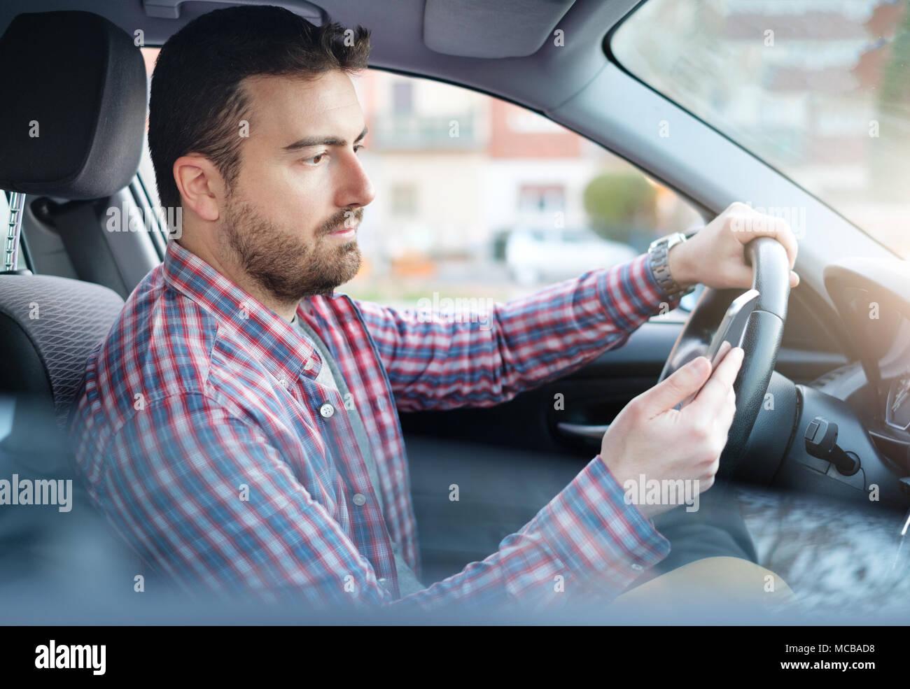 Distratti guy controllando il suo smart phone non si presta attenzione alla strada Immagini Stock