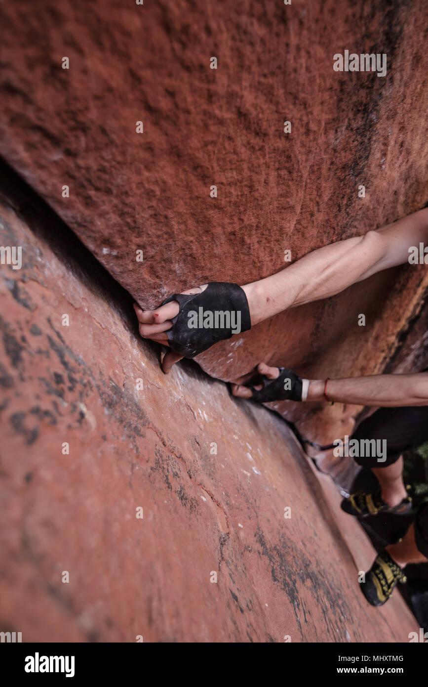 Scalatore di arrampicata su roccia arenaria, mani in presa rock, in elevazione, la calcinazione, nella provincia dello Yunnan in Cina Immagini Stock