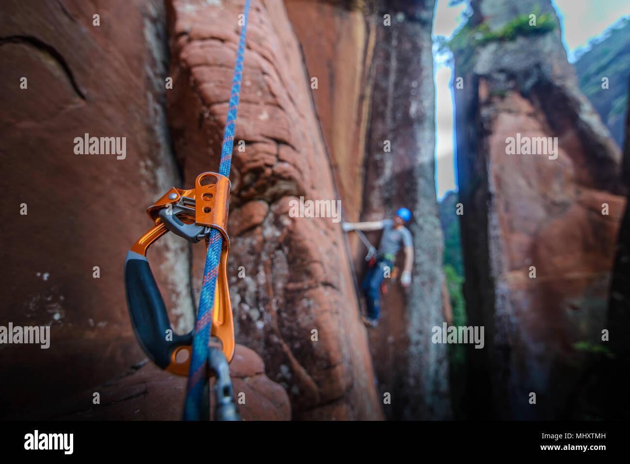Scalatore di arrampicata su roccia arenaria, concentrarsi sulle apparecchiature in primo piano, la calcinazione, nella provincia dello Yunnan in Cina Immagini Stock