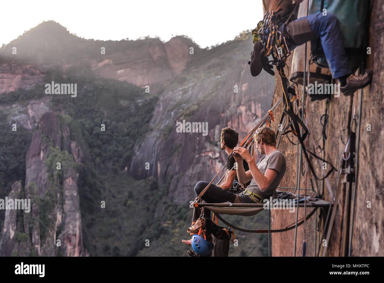 Due arrampicatori udienza del portaledge, guardando a vista, la calcinazione, nella provincia dello Yunnan in Cina Immagini Stock