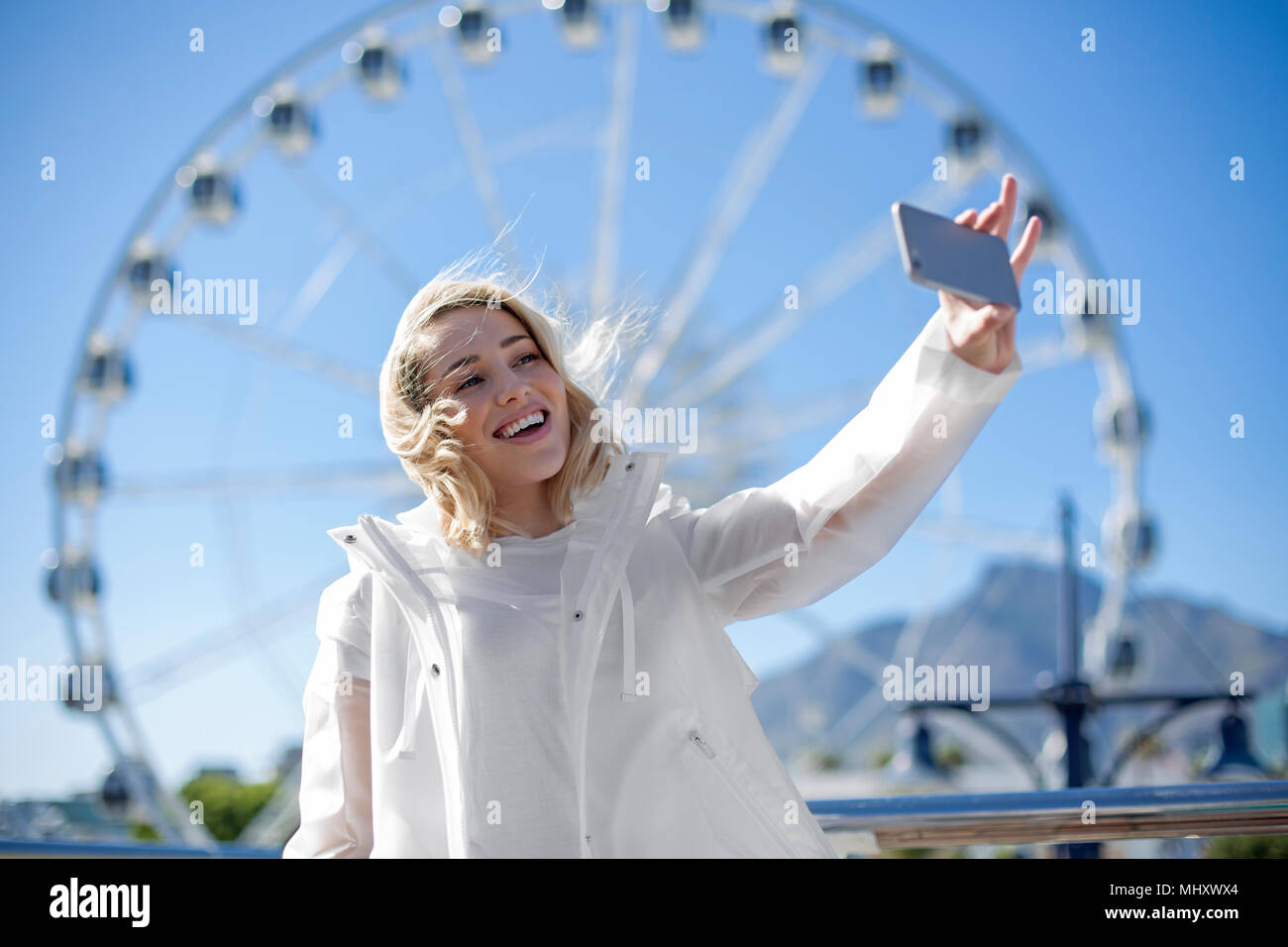 Donna prendendo selfie nella parte anteriore del capo ruota, Lungomare Victoria and Alfred e Cape Town, Sud Africa Immagini Stock