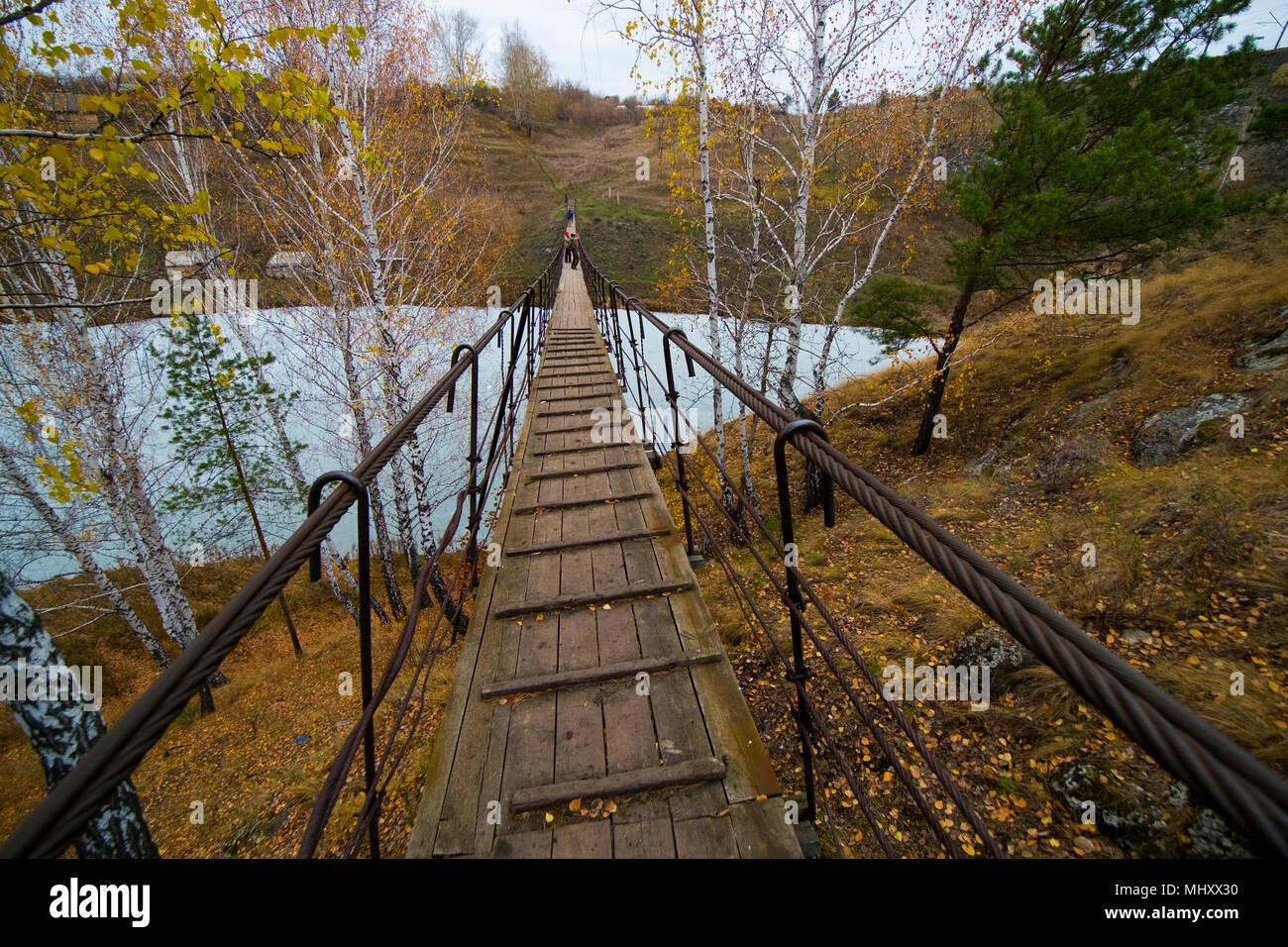 Vista posteriore del piccolo gruppo di escursionisti a piedi su fiume passerella Kislokan, Evenk, Russia Immagini Stock