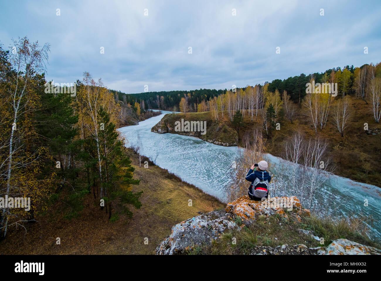 In elevazione posteriore della giovane donna escursionista fotografare fiume dalle rocce, Kislokan, Evenk, Russia Immagini Stock