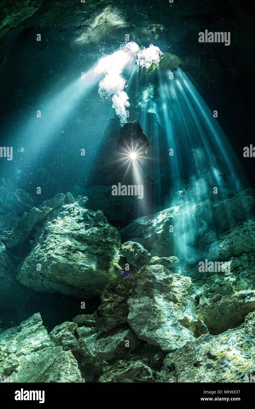Maschio sub immersioni nel fiume sotterraneo (cenote) con raggi del sole e le formazioni rocciose, Tulum, Quintana Roo, Messico Immagini Stock