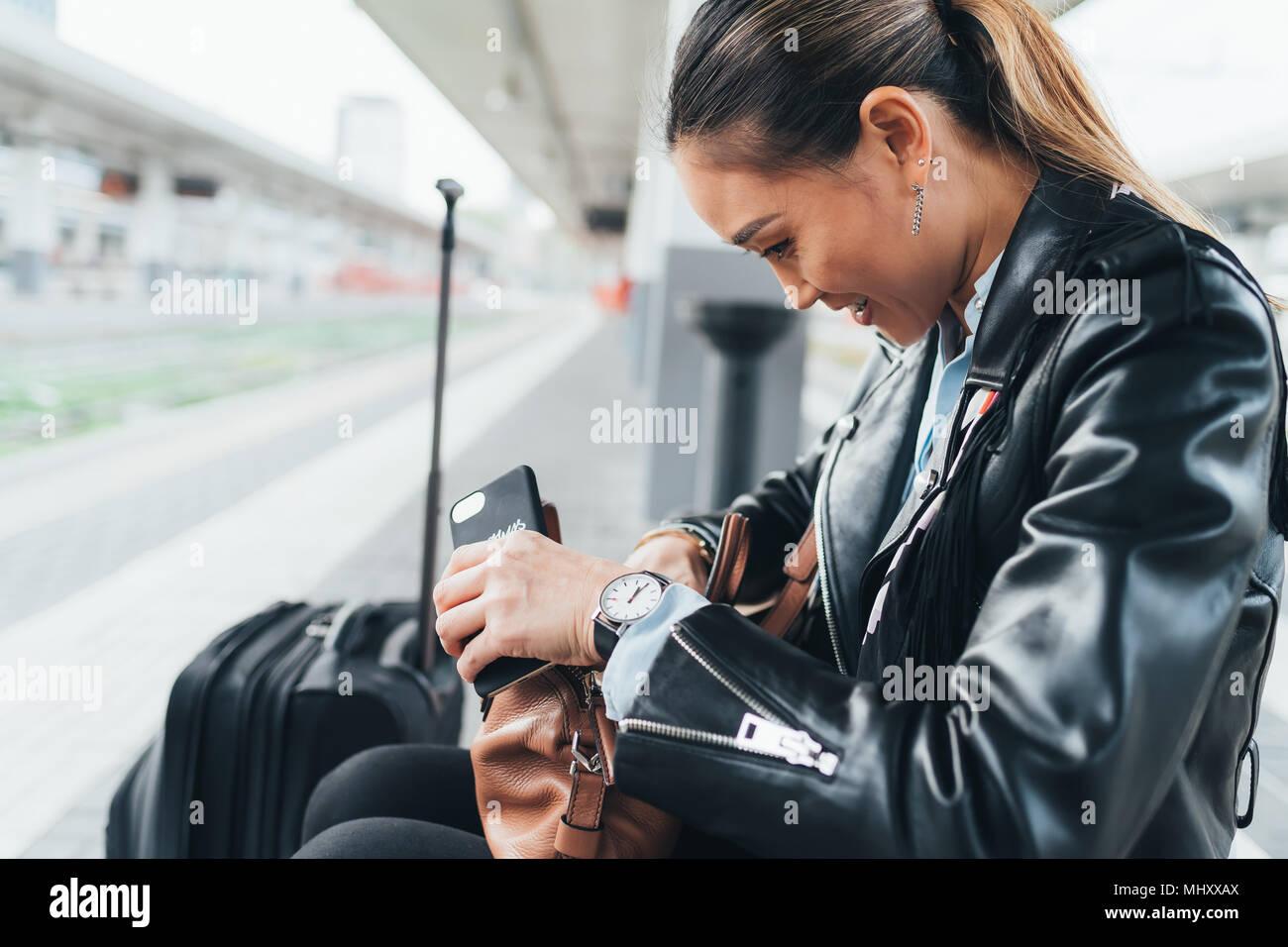 Donna seduta sulla piattaforma del treno, guardando attraverso la borsa, valigia accanto a lei, tenendo lo smartphone Immagini Stock