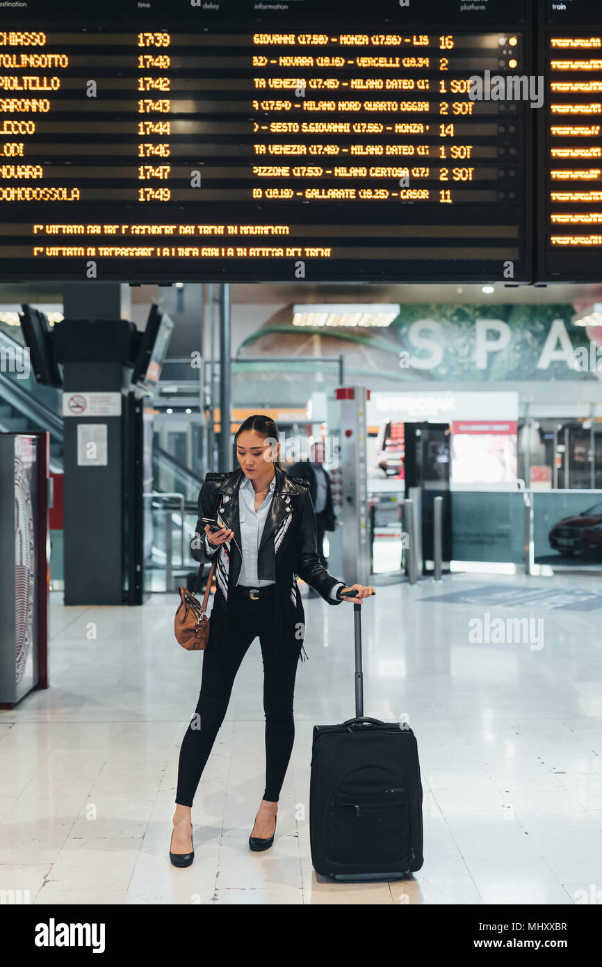 Donna alla stazione ferroviaria, al di sotto del display digitale, tenendo lo smartphone e valigia su ruote Immagini Stock