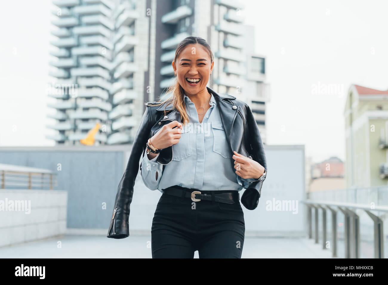 Ritratto di imprenditrice all'aperto, indossa una giacca di pelle attorno alle spalle, ridendo Immagini Stock