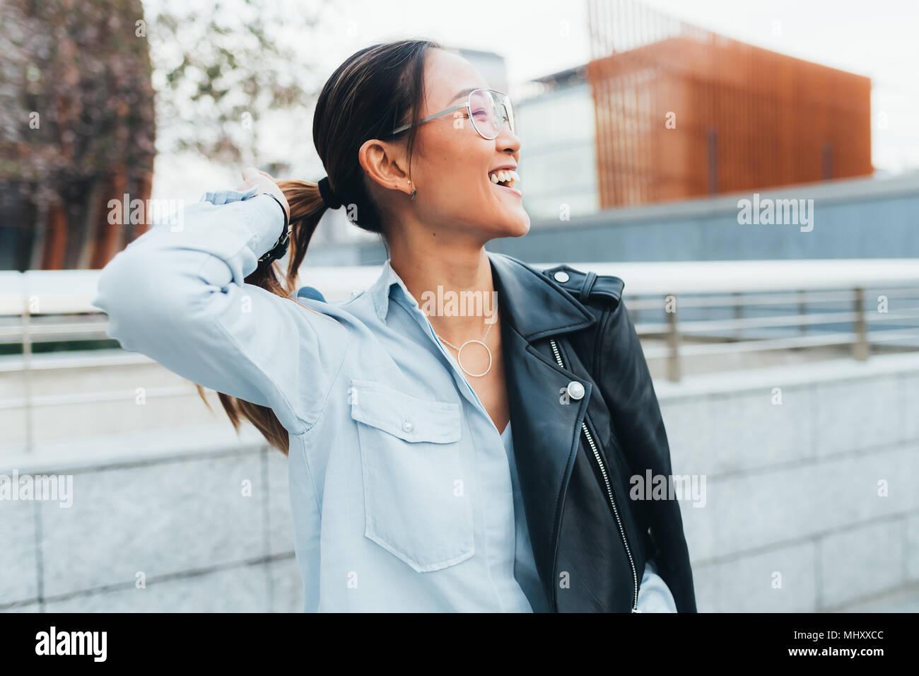 Ritratto di imprenditrice all'aperto, giacca di pelle poggiata sulla spalla, guardando lontano, sorridente Immagini Stock