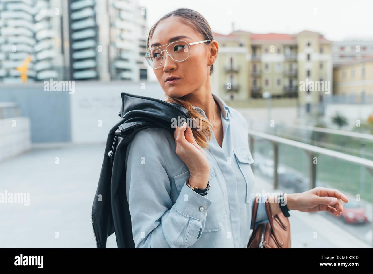 Ritratto di imprenditrice all'aperto portando, giacca di pelle sulla spalla, guardando lontano, pensieroso expression Immagini Stock