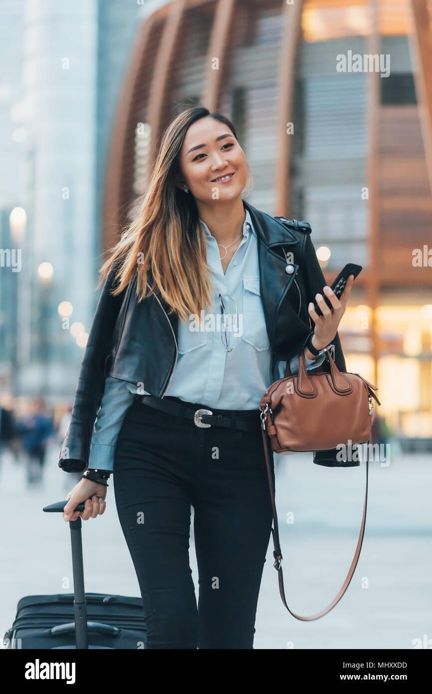 Imprenditrice passeggiate all'aperto tirando la valigia su ruote, tenendo lo smartphone e borsetta, sorridente Immagini Stock