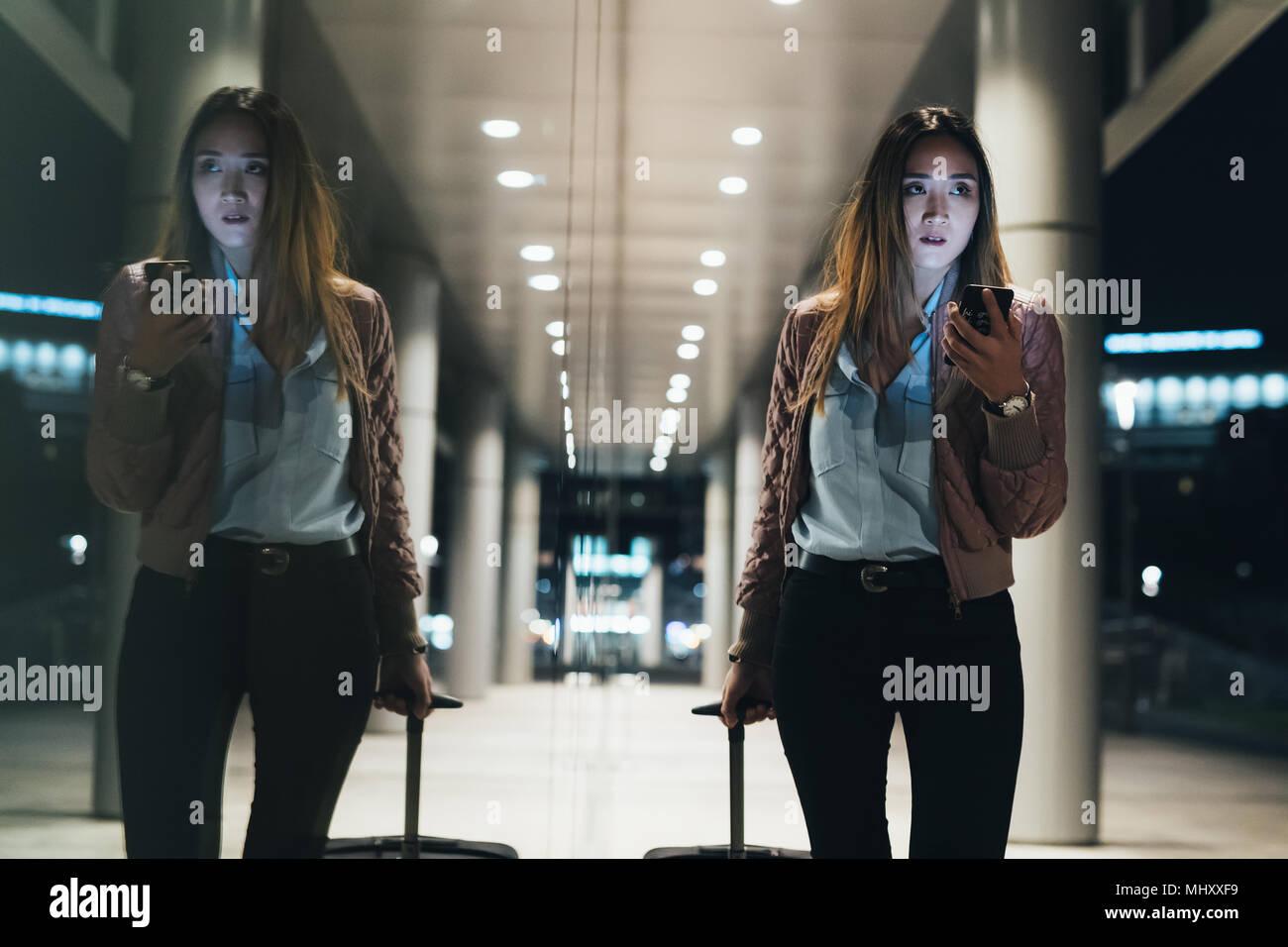 Donna che cammina accanto all edificio moderno di notte, tirando la valigia su ruote, riflessione nella finestra Immagini Stock