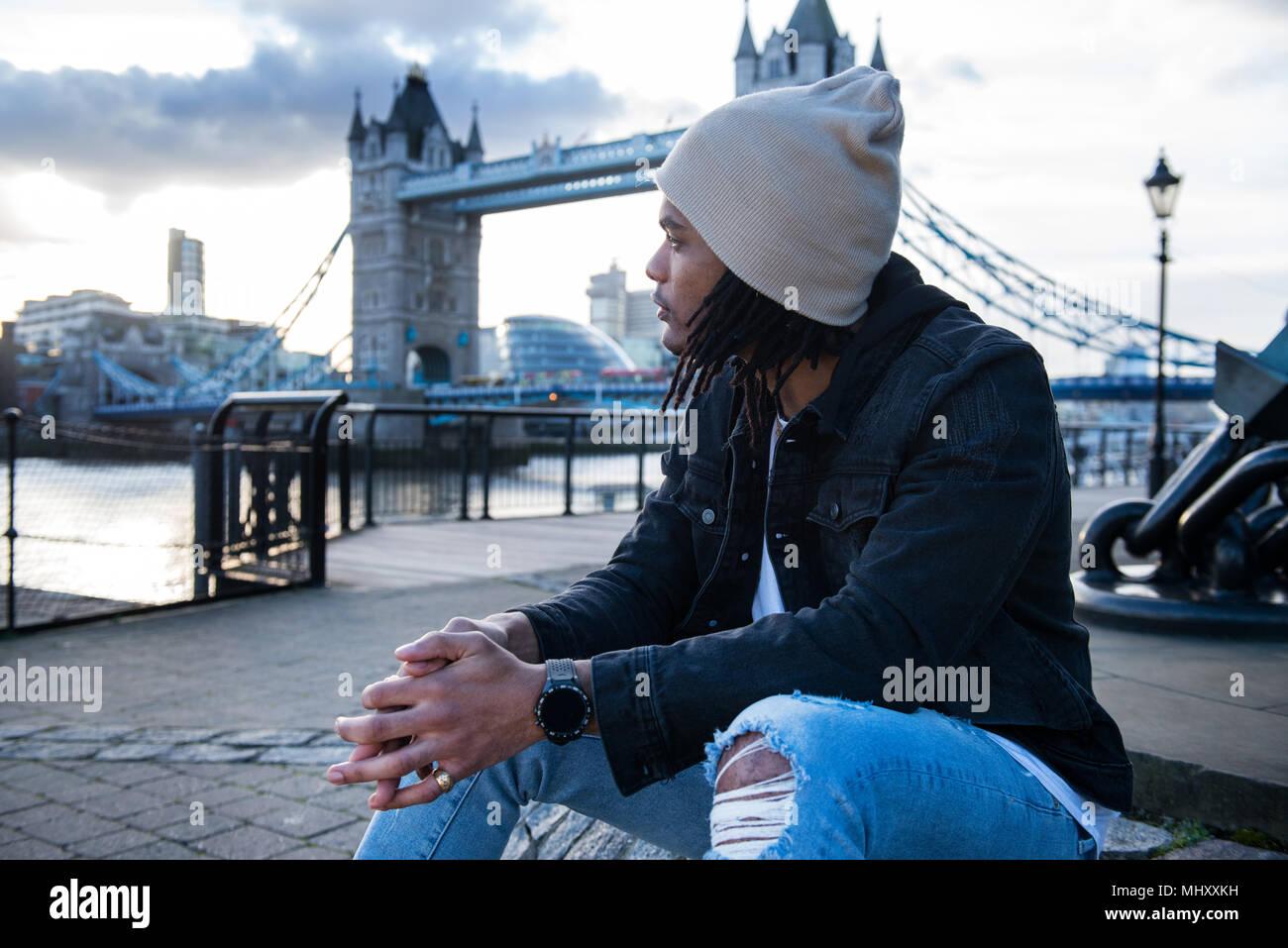 Giovane uomo seduto all'aperto, pensieroso espressioni, Tower Bridge in background, London, England, Regno Unito Immagini Stock