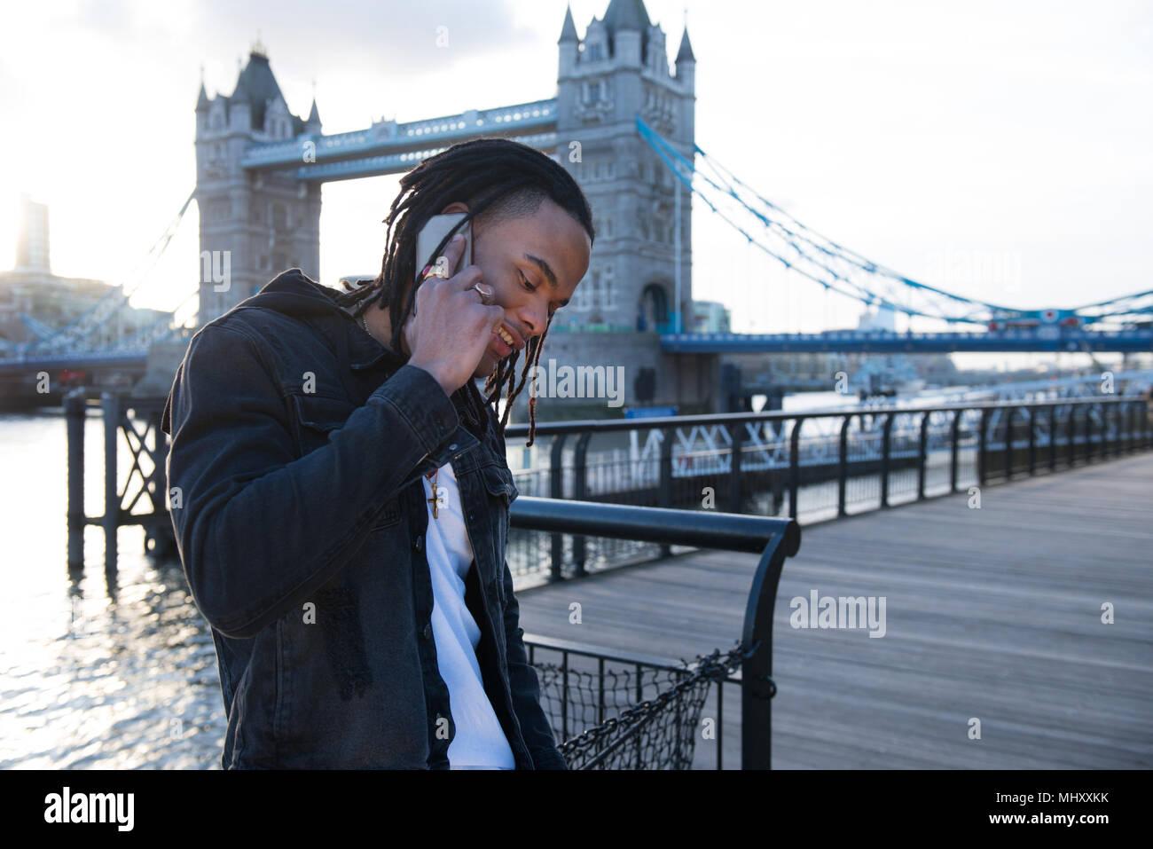 Giovane uomo all'aperto, utilizzando lo smartphone, Tower Bridge in background, London, England, Regno Unito Immagini Stock