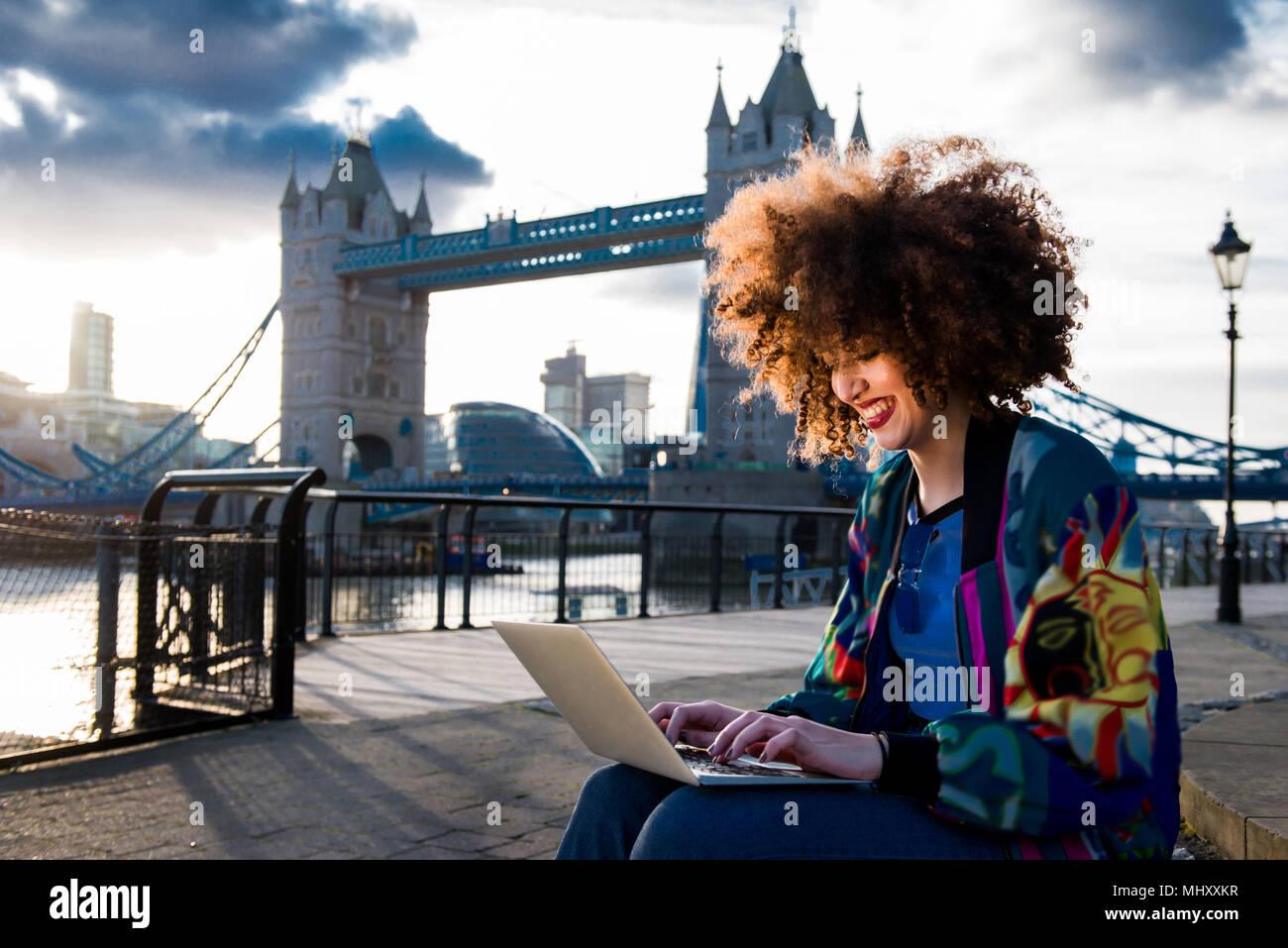Ragazza giovane seduti all'aperto, utilizzando laptop, Tower Bridge in background, London, England, Regno Unito Immagini Stock