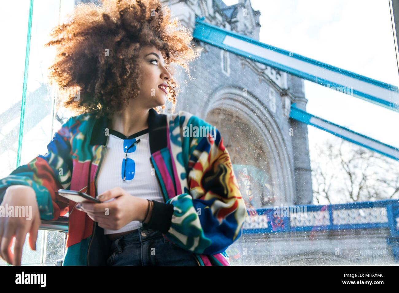Ragazza giovane all'aperto, tenendo lo smartphone, guardando lontano, Tower Bridge in background, London, England, Regno Unito Immagini Stock
