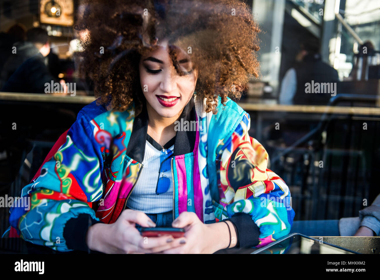 Giovane ragazza seduta nel bar, utilizza lo smartphone, vista attraverso la finestra, London, England, Regno Unito Immagini Stock