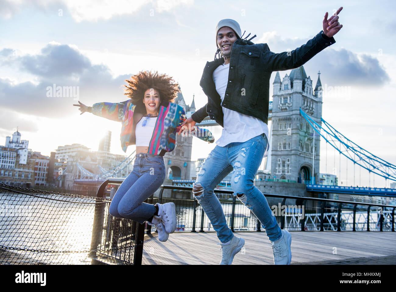 Coppia giovane all'aperto, salti di gioia, Tower Bridge in background, London, England, Regno Unito Immagini Stock