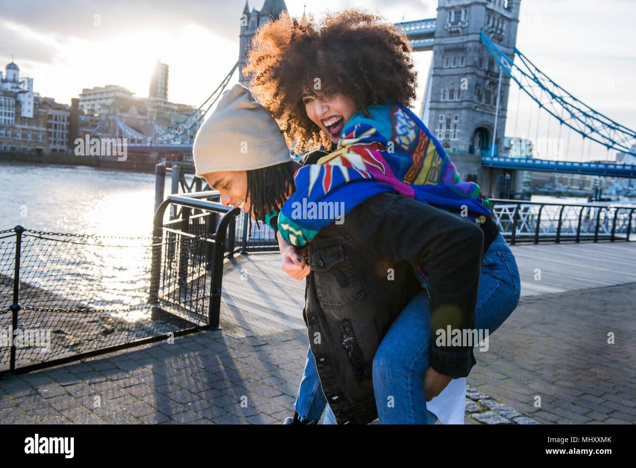 Giovani dando giovane donna sovrapponibile all'aperto, Tower Bridge in background, London, England, Regno Unito Immagini Stock