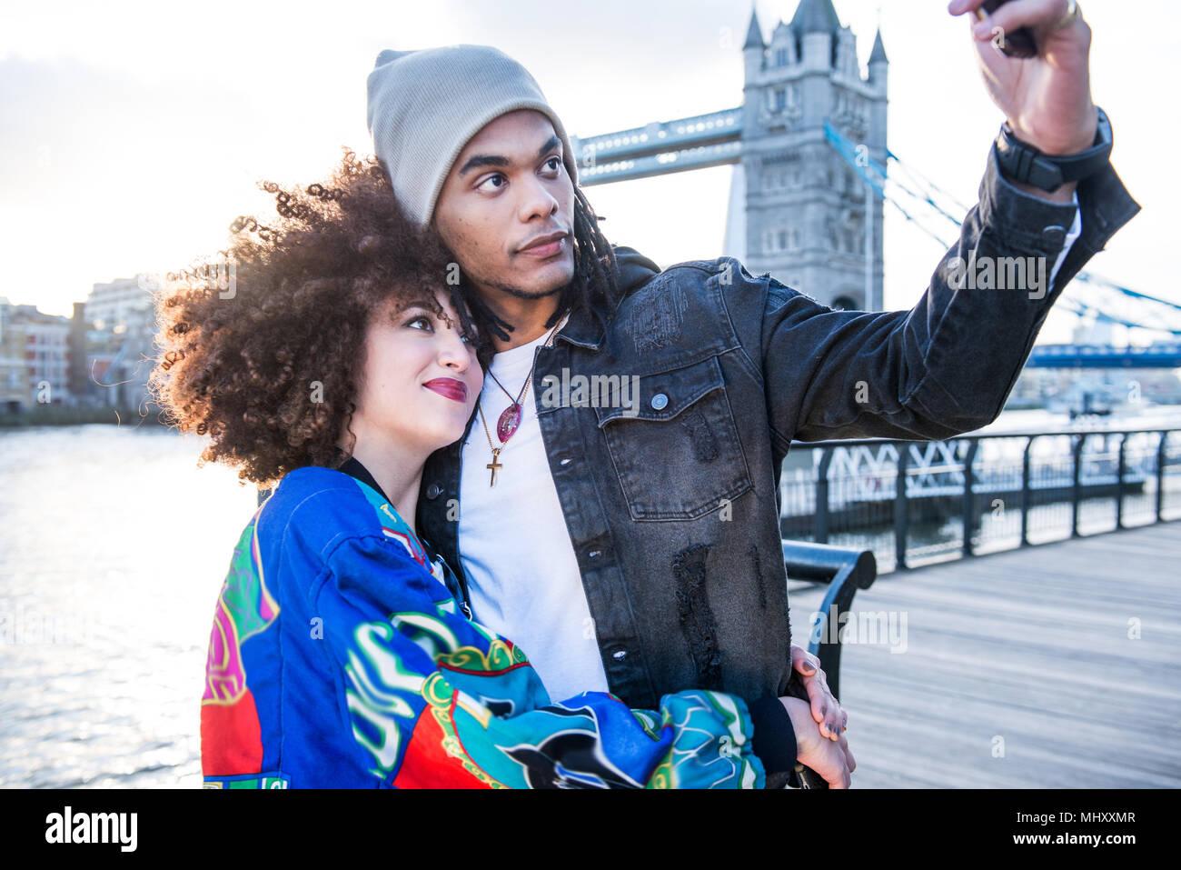Coppia giovane all'aperto, tenendo selfie utilizza lo smartphone, Tower Bridge in background, London, England, Regno Unito Immagini Stock