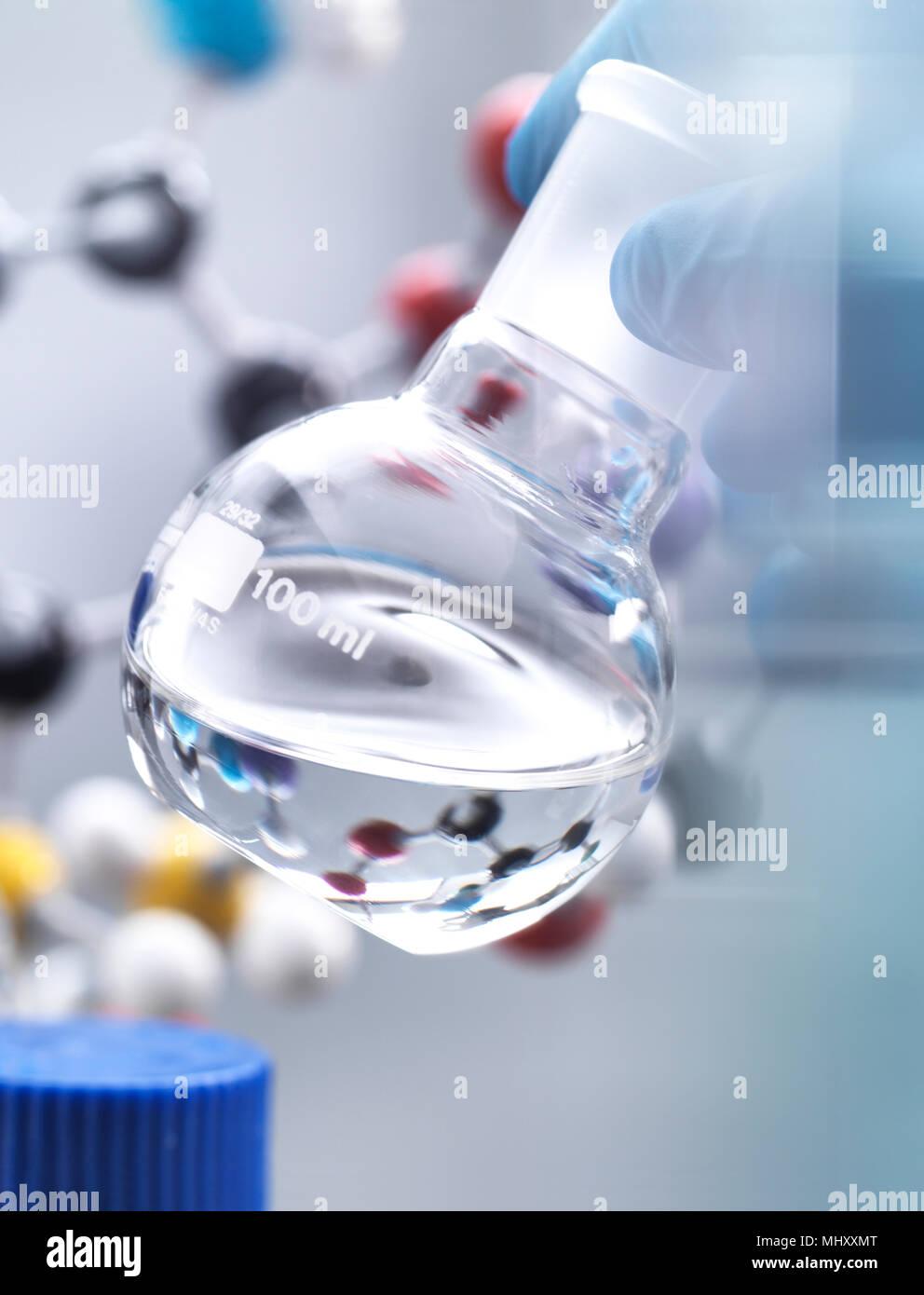 Scienziato preparazione di formula chimica in un pallone da laboratorio durante un esperimento, modello molecolare in background Immagini Stock