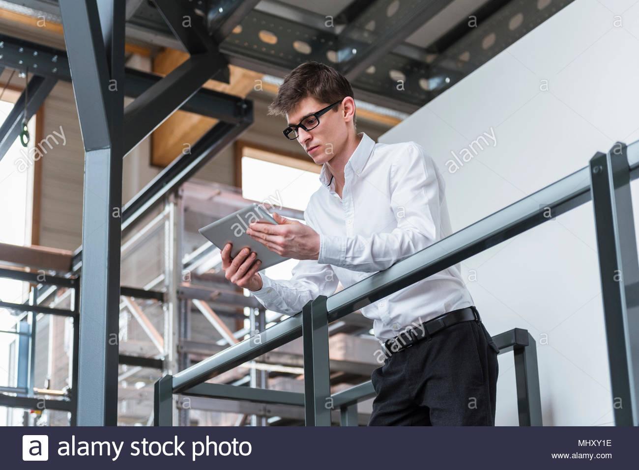 Giovane uomo in piedi in fabbrica, appoggiata sulla ringhiera, utilizzando tavoletta digitale a basso angolo di visione Immagini Stock