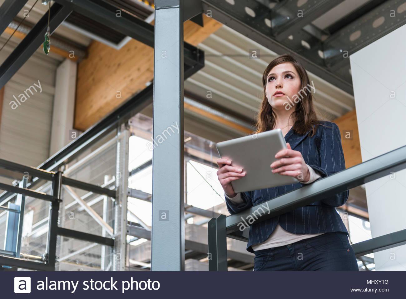 Giovane donna in piedi in fabbrica, appoggiata sulla ringhiera, utilizzando tavoletta digitale a basso angolo di visione Immagini Stock
