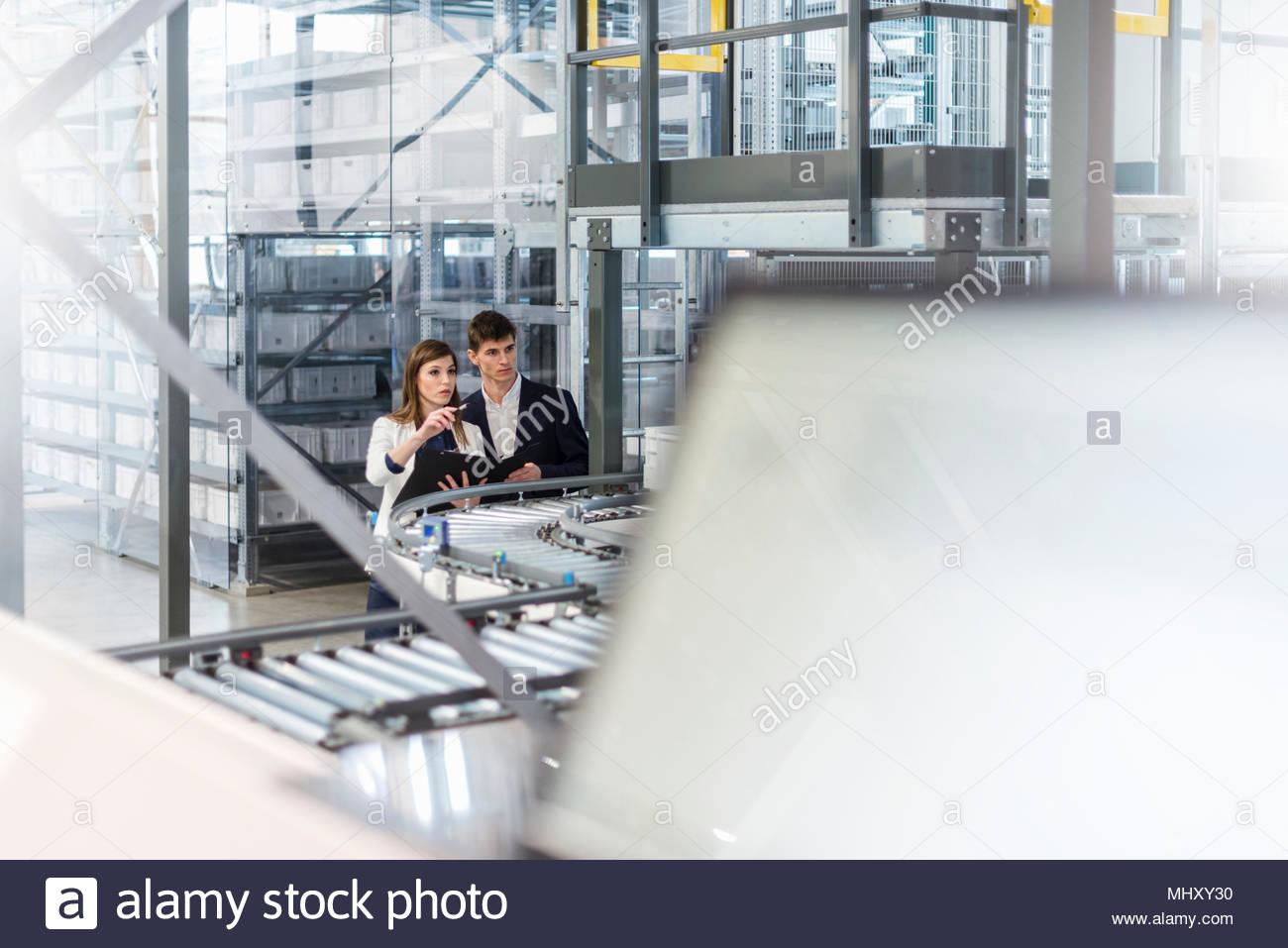 Due colleghi in edificio industriale, avendo discussioni accanto al nastro trasportatore, vista in elevazione Immagini Stock