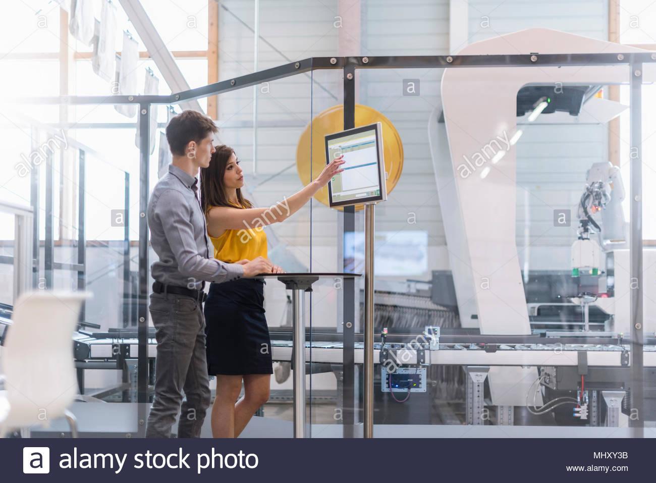 Due colleghi in edificio industriale, avente la discussione, utilizzando il touch screen computer Immagini Stock