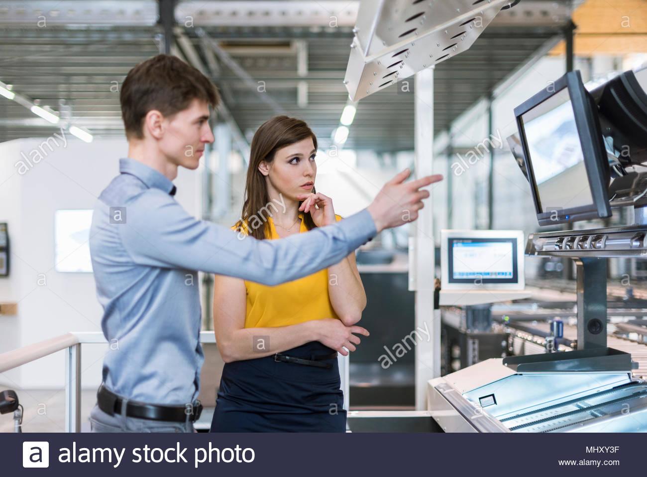 Due colleghi in edificio industriale, avente la discussione, guardando lo schermo del computer Immagini Stock