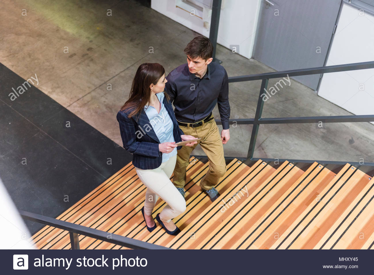 Due colleghi in edificio industriale, salendo le scale, in conversazione, vista in elevazione Immagini Stock