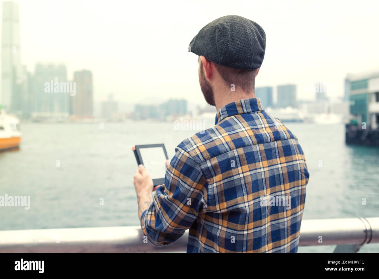 Uomo con tavoletta digitale che guarda lontano in vista del porto, vista posteriore, Hong Kong, Cina, Asia orientale Immagini Stock