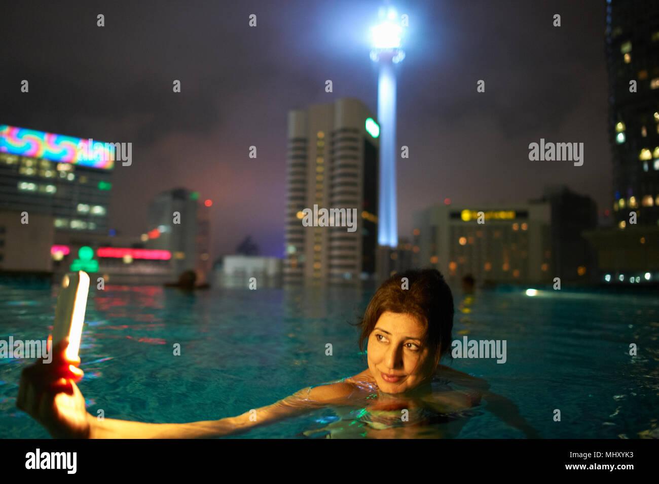 Turistica prendendo selfie nella piscina sul tetto, KL Tower in background, Kuala Lumpur, Malesia Immagini Stock