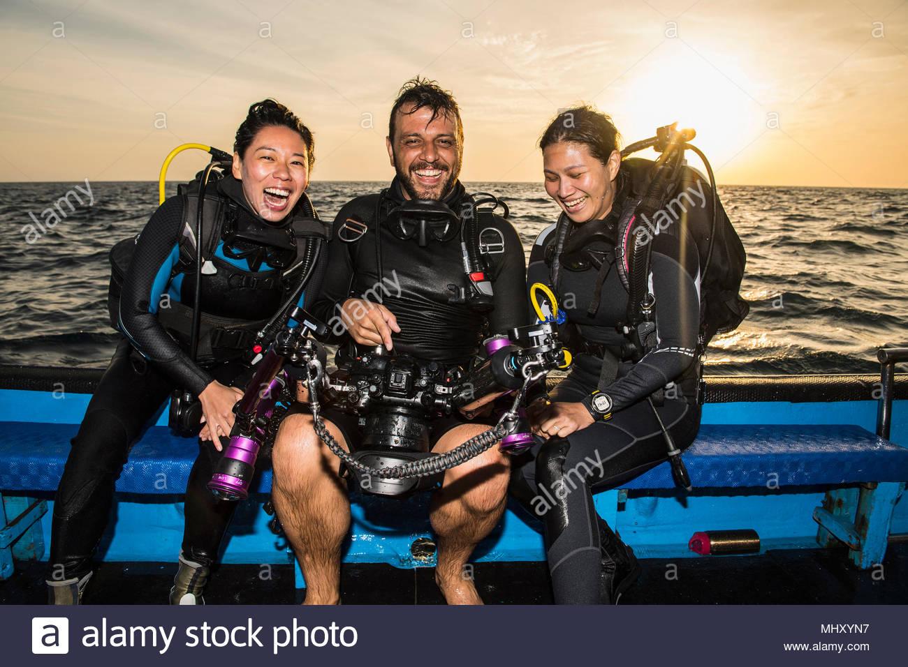 Amici guardando le immagini sulla fotocamera subacquea dopo immersione, il Parco Naturale di Tubbataha Reef, Mare di Sulu, Filippine Immagini Stock