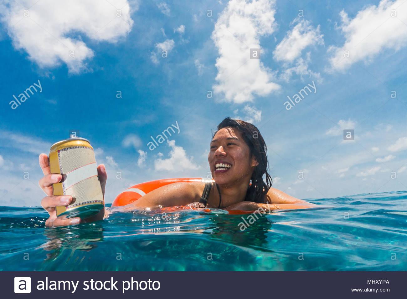 Donna galleggianti in mare su anello di salvataggio, godendo di conserve di bere, il Parco Naturale di Tubbataha Reef, Mare di Sulu, Filippine Immagini Stock