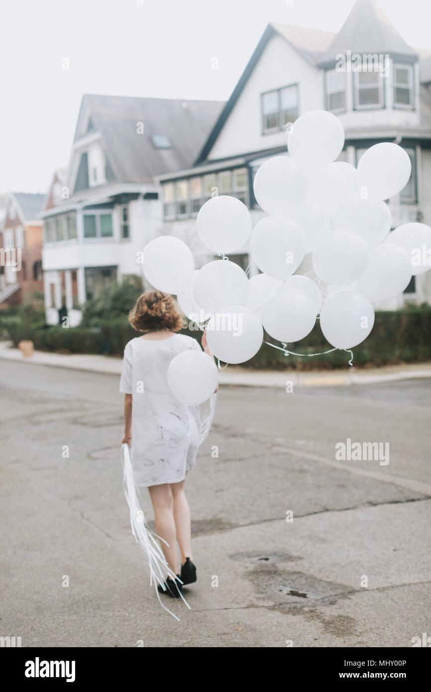 Donna in strada tenendo mazzetto di palloncini, vista posteriore, Boston, Massachusetts, Stati Uniti Immagini Stock