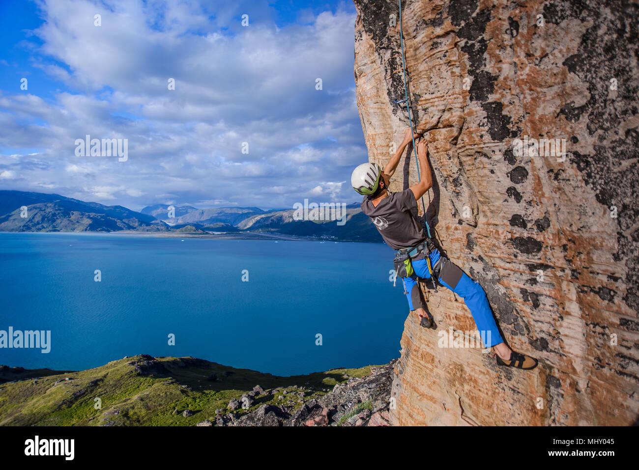 Giovane maschio scalatore di pietra arenaria di arrampicata rockface, Narsaq, Vestgronland, Groenlandia meridionale Immagini Stock