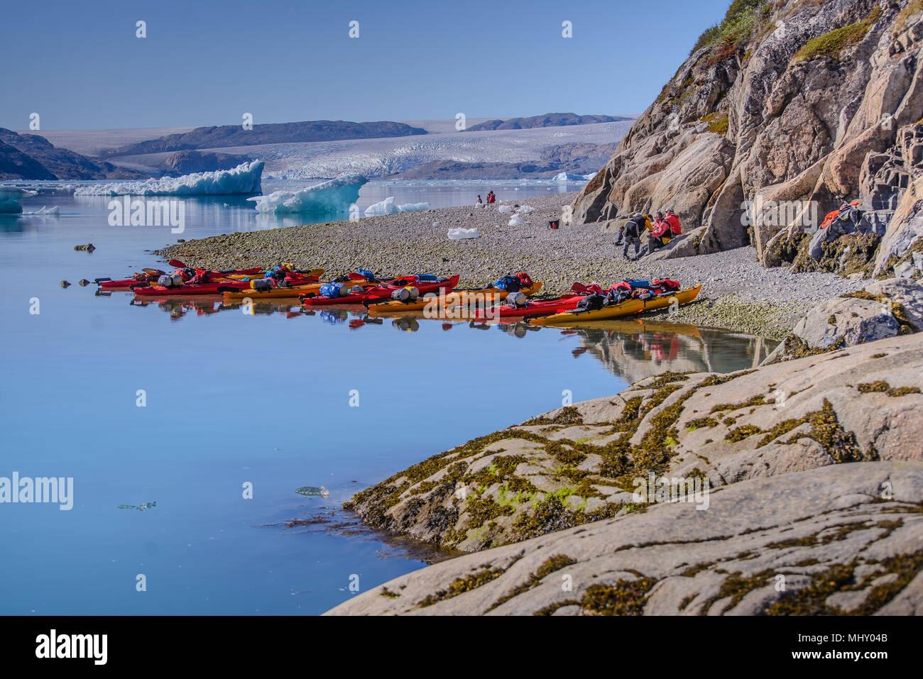 Avventura turisti sulla spiaggia del fiordo con righe di kayak, Narsaq, Vestgronland, Groenlandia meridionale Immagini Stock