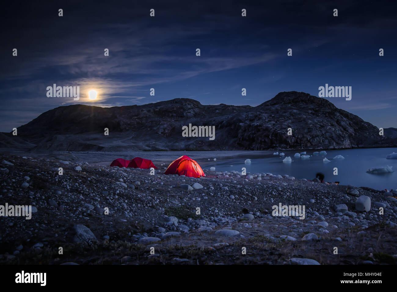Paesaggio con tende dai fjord e luna piena di notte, Narsaq, Vestgronland, Groenlandia meridionale Immagini Stock