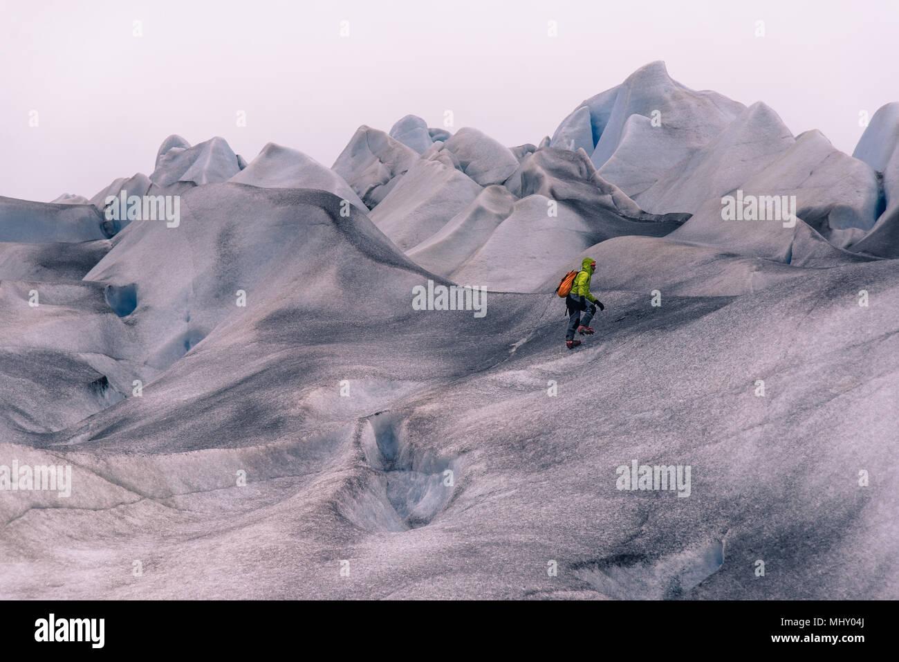 Escursionista maschio escursionismo su grigio paesaggi innevati, Narsaq, Vestgronland, Groenlandia meridionale Immagini Stock