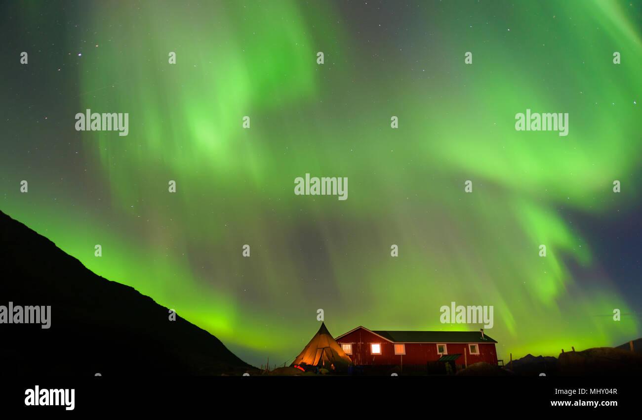 Paesaggio con log cabin e aurora boreale di notte, Narsaq, Vestgronland, Groenlandia meridionale Immagini Stock