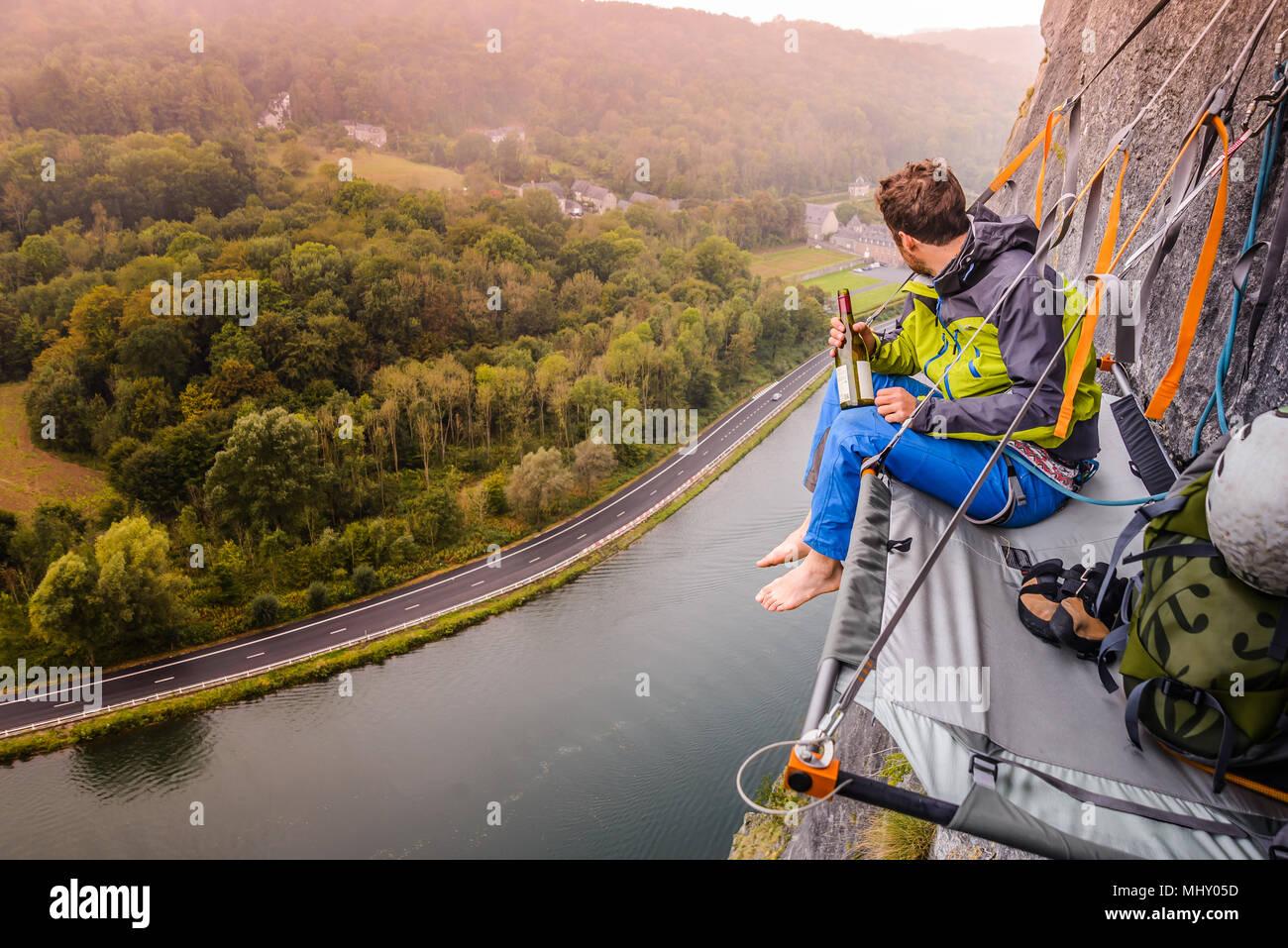 Giovane maschio rocciatore seduta di roccia portaledge sopra fiume Mosa, Freyr, Belgio, vista in elevazione Immagini Stock